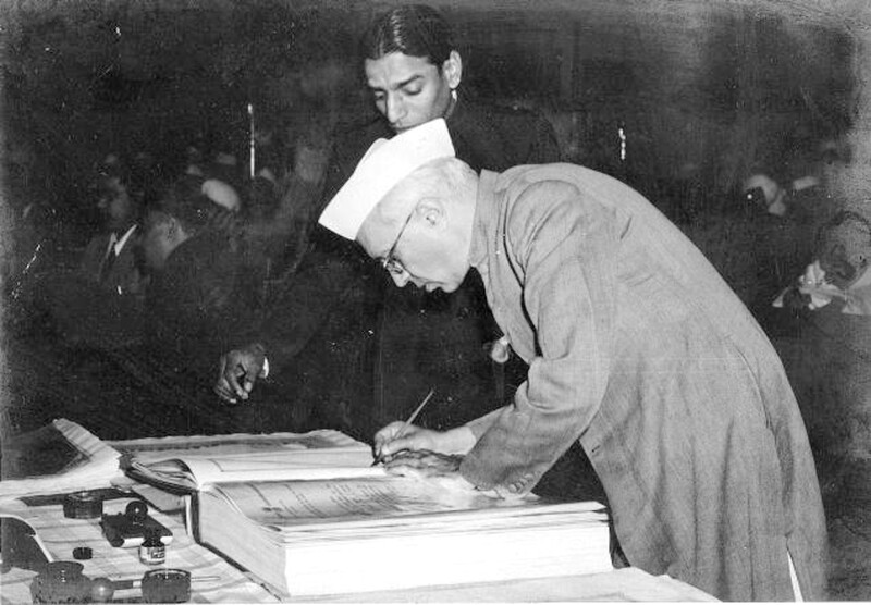 Prime Minister Pt. Jawaharlal Nehru signing a copy of the Indian Constitution (1950)